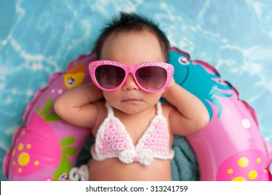 Nine day old newborn baby girl wearing pink sunglasses and a pink and white bikini. She is sleeping on a tiny inflatable swim ring.