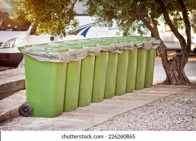 nine green containers collecting trash at camp