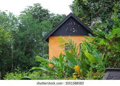 Nine Mile, Jamaica 10/8/2017 House on the hillside, just outside the Bob Marley Mausoleum compound. Building is partially obscured by lush, green foliage.