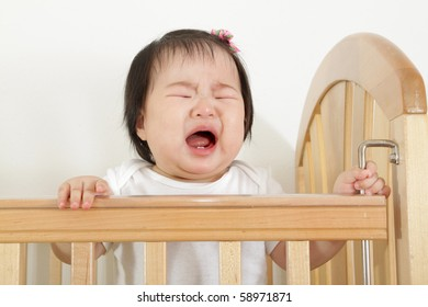 nine month old asian baby infant girl crying and bawling in wooden crib