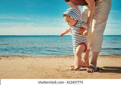 Nine month old baby boy walking on the beach in beautiful summer day