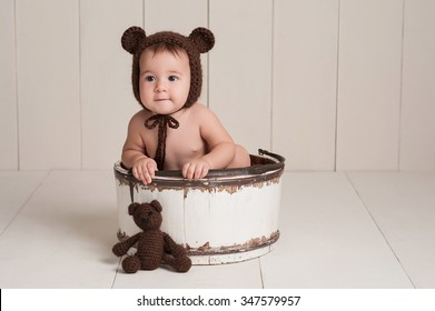 Nine month old newborn baby girl wearing a brown, crocheted bear hat. She is sitting in a white, wooden bucket and has a stuffed bear toy. Shot in the studio on a white, wood paneled background.