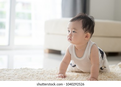 Nine months old baby boy crawling on floor. Asian family at home, living lifestyle indoors.