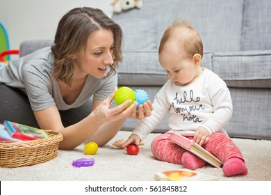 Nine months old baby girl playing with her mother on the floor