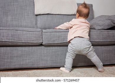 Nine months old baby girl standing on her feet in an effort to climb up the sofa; baby just learnt how to stand on her feet