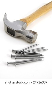 Nine Nails and a metal hammer with wood handle on a white background.