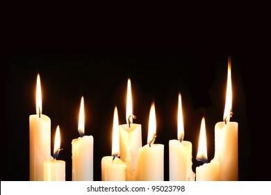 Nine ordinary lighting candles in a row on black background