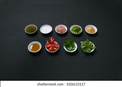Nine of Thai green curry ingredients put in a small bowl on blackboard background.