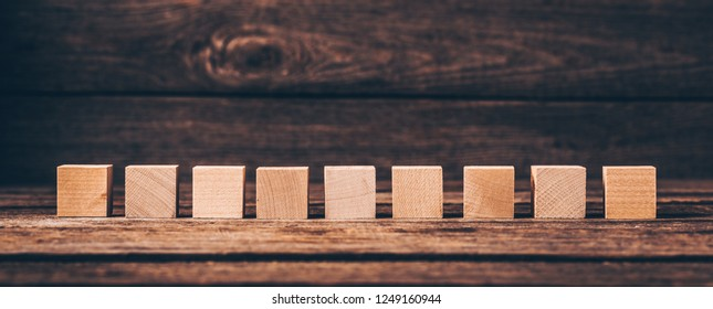 Nine Wooden Cubes on Wood Background with Copyspace