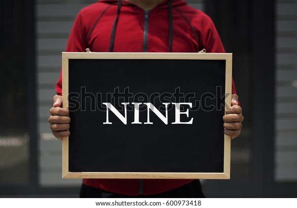 nine written on blackboard with someone is holding it
