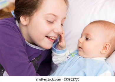 Nine year old girl amusing her little baby sister, sharing some tender and affectionate moments together, smiling, having fun.