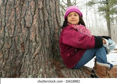 Nine year old girl enjoying sitting under tree in winter