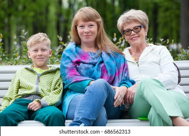 Nine years old boy with an elderly grandmother and a young mother sitting on a park bench