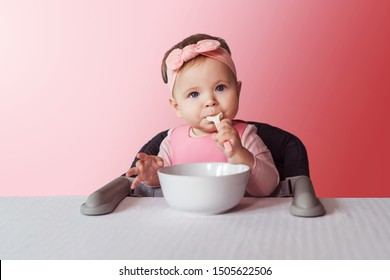 Nine-month-old smiling baby girl in pink bandage on her head sits at white table in highchair and eats herself with spoon from bowl. Pink background. Healthy eating for kids. Child's nutrition.