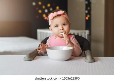 Une petite fille souriante de neuf mois en bandage rose sur la tête est assise à une table blanche en chaise haute et se mange avec une cuillère de bol.Arrière-plan flou. Manger sainement pour les enfants. La nutrition de l'enfant.