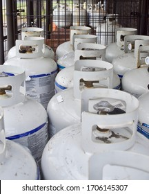 Nineteen propane cylinder tanks staged in metal cage ready for sale.
