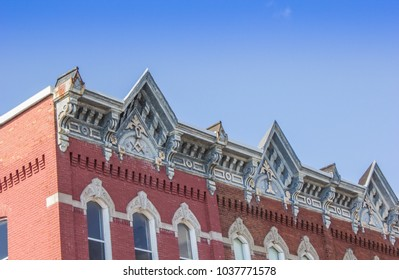 A nineteenth century brick building with a decorative cornice stands under a blue sky in the historic town of Brockville, Ontario, Canada.