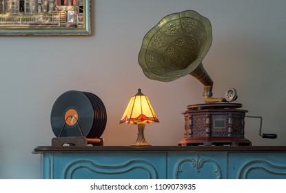 Nineteenth century phonograph (gramophone) and vinyl records on a wooden table and background of beige wall and hanged painting