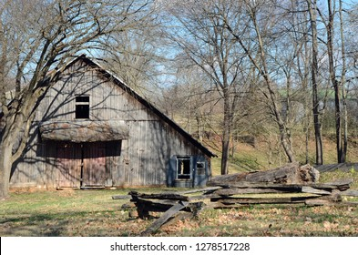 Nineteenth century pioneer wood barn on a farm with traditional timber frame construction covered with vertical board siding.