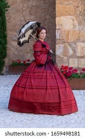 Nineteenth-century woman, elegantly dressed, walks through the courtyard of a castle