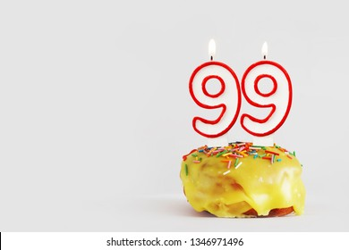 Ninety nine years anniversary. Birthday cupcake with white burning candles with red border in the form of 99 number. Light gray background with copy space