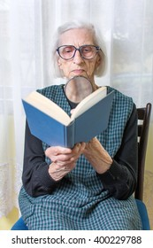 Ninety years old grandma reading a book through magnifying glass