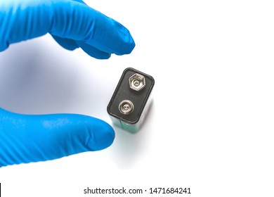 A nine-volt battery in hand on a white background. The electrician's hand in the rubber glove holds the AAA batteries for replacement. Plus mark (sign)