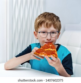 A nine-year-old boy with glasses eats pizza.