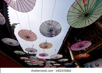 Ningbo/China-May 2019: perspective view of many oiled paper umbrellas hanging in the air of Chinese ancient town. Wide angle. Popular Chinese handicraft
