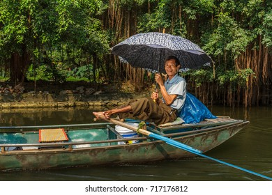 NINH BINH, VIETNAM - 5/6/2016: A smiling boat guide paddles down the Ngo Dong River, near Tam Coc village, at Trang An UNESCO World Heritage site in Ninh Binh, Vietnam.