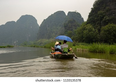 Ninh Binh, Vietnam - April 17, 2018: Tourists take a boad trip on the Tam Coc river.Usually female boat drivers drive the boats like many other places in Vietnam.