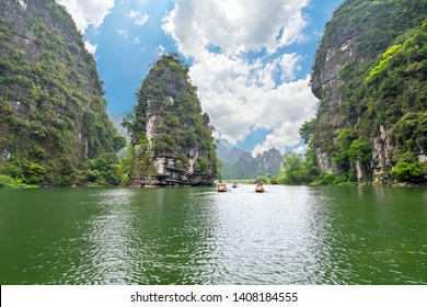Ninh Binh, Vietnam - April 5th, 2019: People rowing boats for carrying tourists on Ngo Dong river of the Tam Coc National Park. Tam Coc is a popular tourist destination in Ninh Binh, Vietnam.