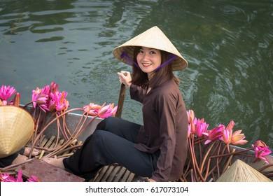 Ninh Binh, Vietnam - Oct 9, 2016: Portrait Vietnamese girl sits on boat wearing conical hat, in Yen stream