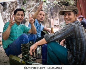 Ninh Binh/Vietnam - 03/19/2019: Three happy Vietnamese workers men showing peace symbol with their fingers, having lunch break and smoking classic bamboo tube pipe, Tam Coc, Vietnam