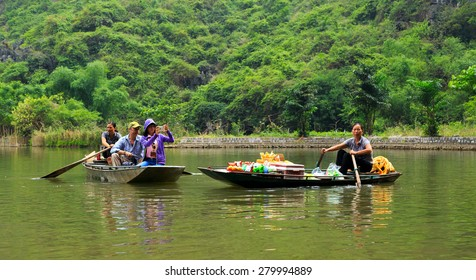 """NINHBINH, VIETNAM - May 17, 2015: Unidentified Vietnamese persons on the Floating Market at """"Ngo Dong"""" river in Tam Coc Bich Dong heritage, NinhBinh province, Vietnam."""