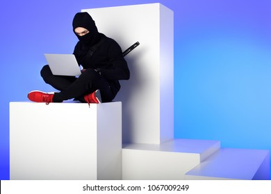 ninja in black clothing using laptop while sitting on white block isolated on blue