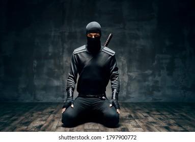 Ninja kneeling posing with a sword over black background. japanese fighter concept
