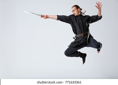 A ninja man jumping forward with swords in his outstretched hand against a gray background