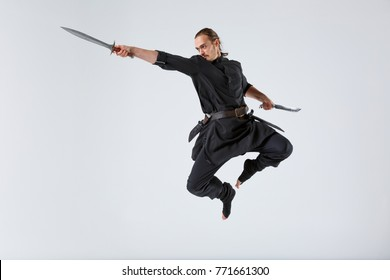 A ninja man jumping with a knife and attacking with a sword on a gray background