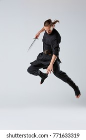 A ninja man jumping with a sword pointed down on a gray background. Front view
