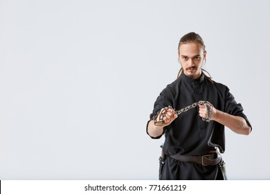 A ninja man pulls a chain between his fists against a gray background