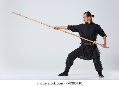 A ninja man, is in a special black kimono, works out the technique of striking with a fighting bamboo stick.