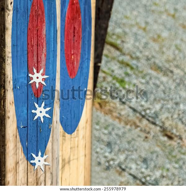 Ninja metal or steel shurikens hitting blue and red wood target