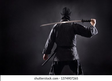 Ninja samurai with katana stands with his back to the viewer.