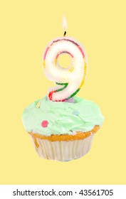 ninth birthday cupcake with green frosting on a yellow background