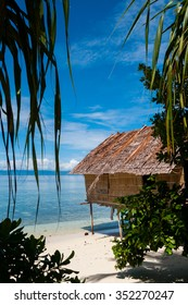 Nipa Hut on stilts at a Beautiful white sand beach Beach in front of the ocean in Raja Ampat, Papua New Guinea