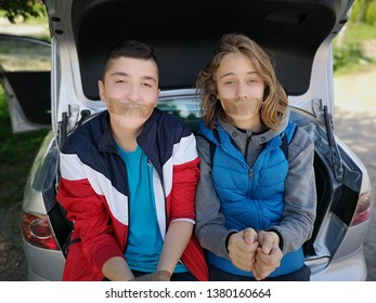 Nis, Serbia, April 25th, 2019 / Hostages sitting on the trunk of the car with hands and mouth tied up with tape