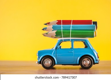 NIS, SERBIA - JANUARY 8 2018: Miniature figure toy car Mini Morris carrying colored pencils on roof on yellow background in studio. Education and art concept.