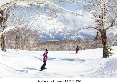 NISEKO, JAPAN - MARCH 10 : General view of people snowboarding on a tree-lined piste in the Niseko Grand Hirafu ski resort, Hokkaido, Japan on 10th March 2012. Mt Yotei can be seen in the background.