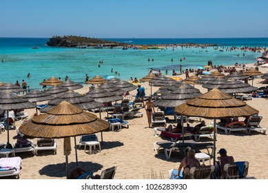 NISSI BEACH, AYIA NAPA, CYPRUS - JUNE 15, 2017: Tourists relaxing on the beach in the summer vacation. Nissi beach is one of Cyprus most famous beaches with white sand